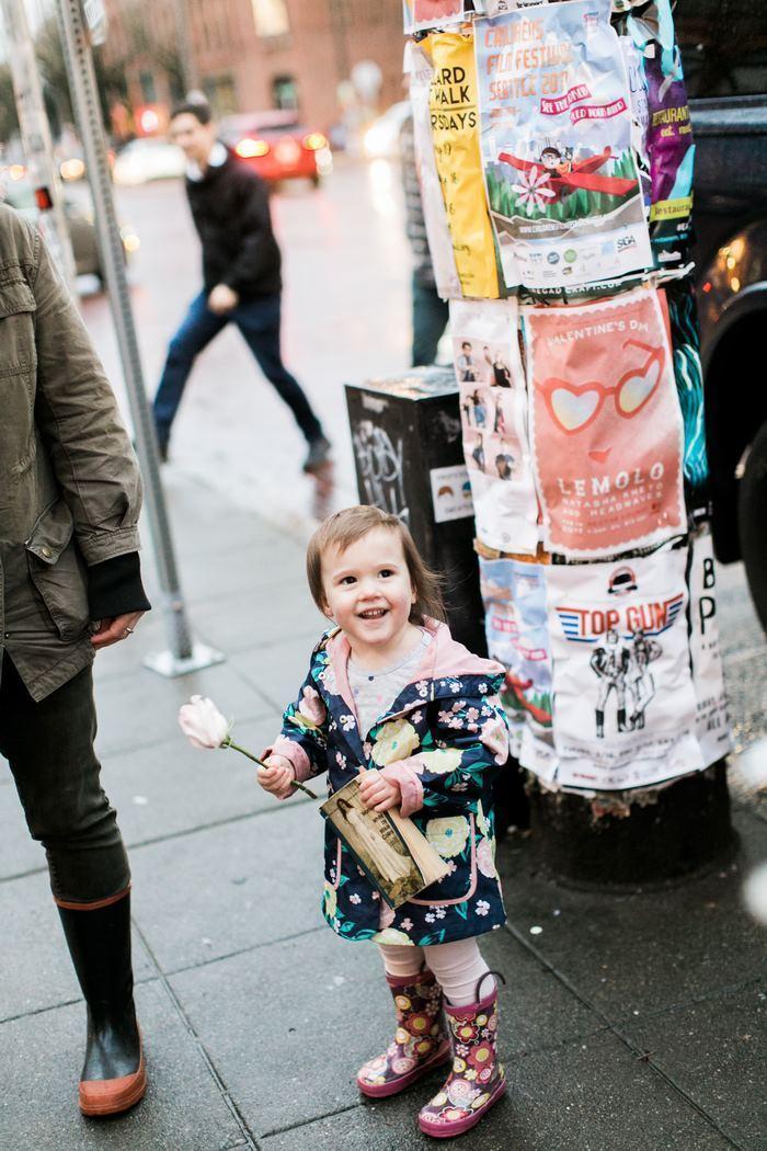 A garotinha sorrindo com a flor que ganhou de presente em mãos