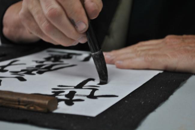 mão escrevendo em caligrafia japonesa